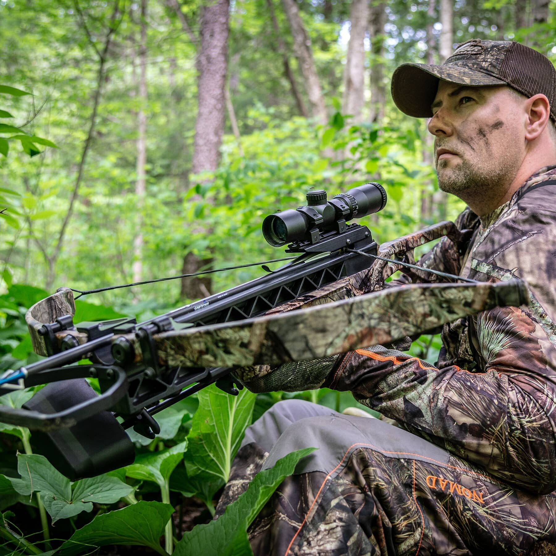 hunter sitting in the woods holding a matrix g340
