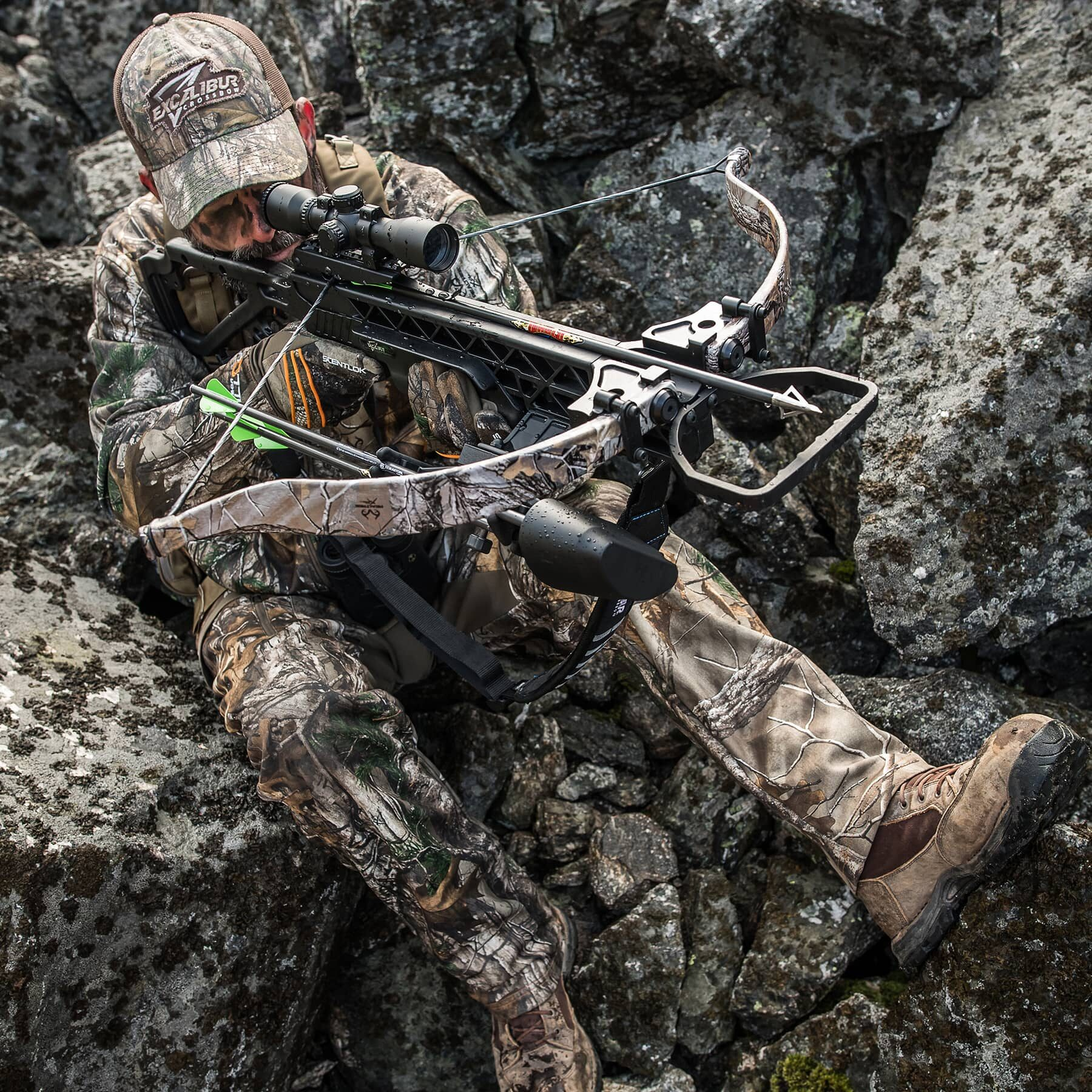 hunter sitting amongst rocks aiming the grz 2