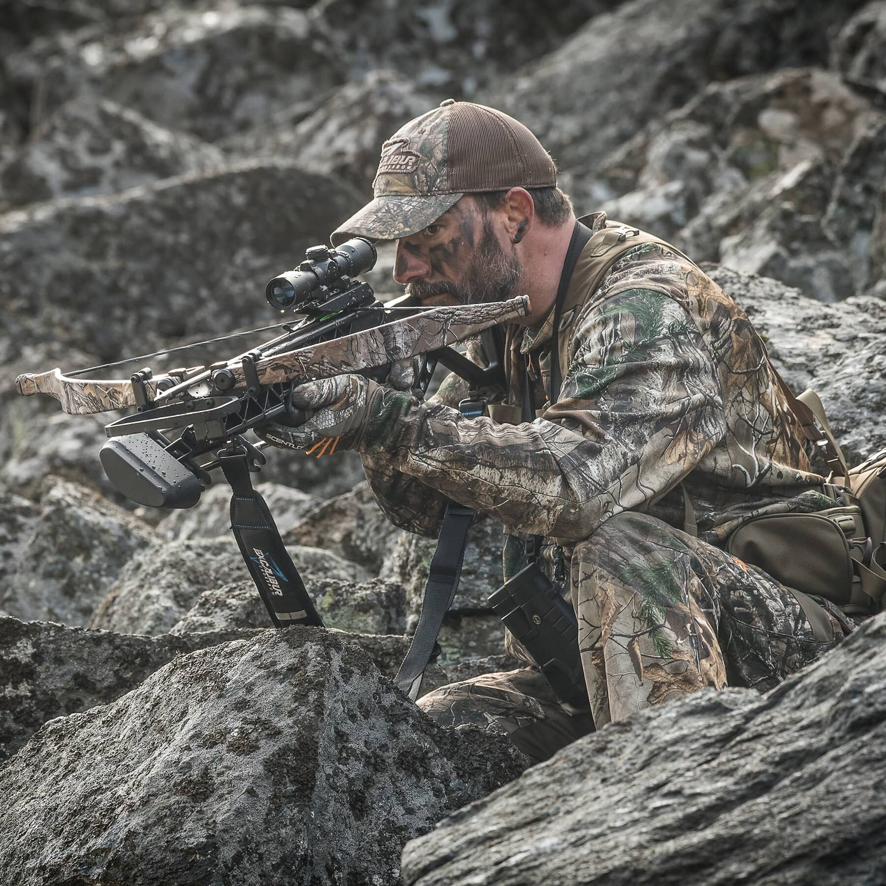 hunter crouched amongst rocks, aiming the grz 2
